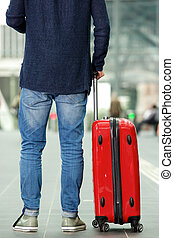Man with traveling bag standing at train station - Rear...