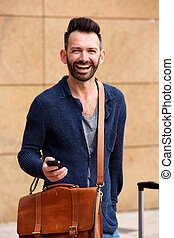 Handsome mature man standing outdoors and laughing