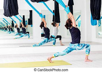 Women doing realigning yoga exercise.
