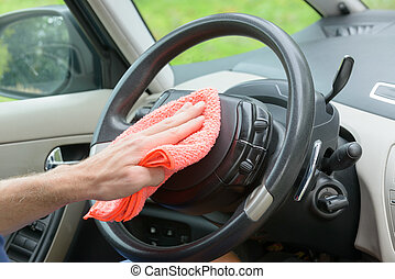 Cleaning car interior - Hand with cloth cleaning car...