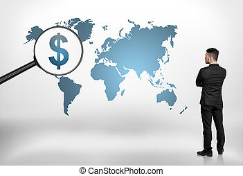 Back view of a businessman looking at world map with big...