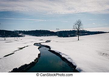 Small stream through a snow covered farm field in rural...