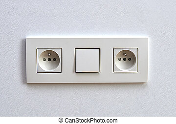White light switch and electrical outlet in front of white...
