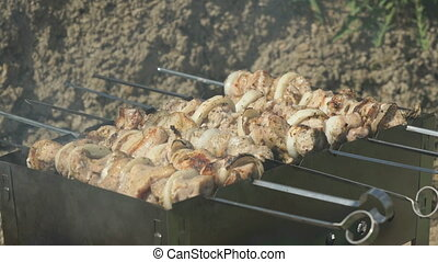 Frying of marinated meat on metal skewers on coals - Frying...