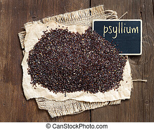 Psyllium seeds with a small chalkboard on wooden background
