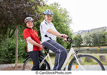 Portrait Of Couple Riding Bicycle - Portrait Of Smiling...