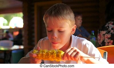the beautiful child eats boiled corn