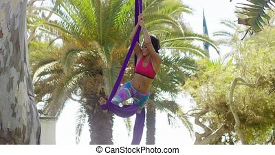 Young gymnast working on her acrobatic dance routine hanging...