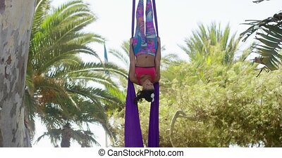 Attractive sporty acrobatic dancer working out on a pair of...