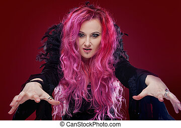 Scary witch with red hair performs magic. Halloween. - Scary...