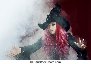 Attractive woman in witches hat with red hair performs...