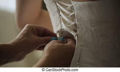 Close up view of woman tighten corset of wedding dress....