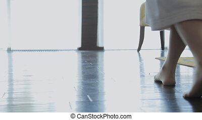 Down leg view of woman walking in room with bare foot.