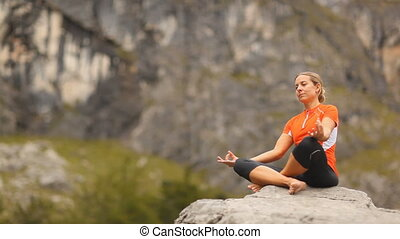 woman practicing yoga on rock