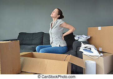 Woman suffers from back pain due to unpacking boxes - Woman...