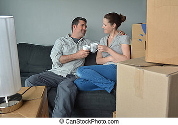 Happy couple relax on a sofa during a move into a new home -...