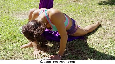 Fit young woman working out doing press-ups on the grass in...