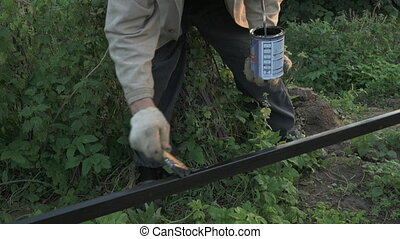 Old man 70s paints the iron fence using a black