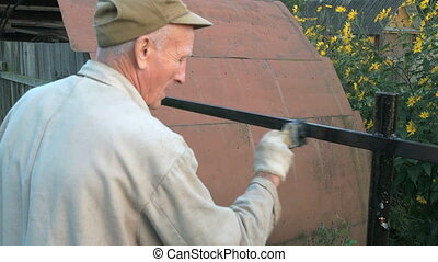 Aged man 60s paints the iron fence using a black paint...