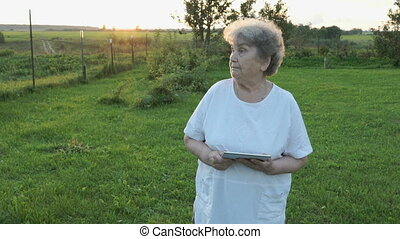 Aged woman 80s holding computer tablet outdoors - Aged woman...