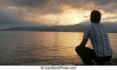 The man looks in a shirt looking at the sunrise on the beach of the ocean. The sun rises from behind the mountains. The concept of nature admiration