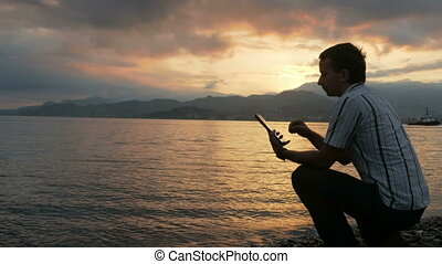 A man in a shirt checks messages on the tablet during the sunrise on the beach of the ocean. Wonderful colors of the sky and the rising of the sun from behind the mountains.