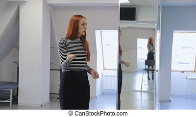 Ginger woman in striped blouse stands in middle of dancing...