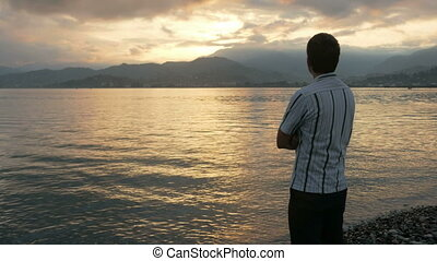 The man looks in a shirt looking at the sunrise on the beach...