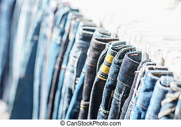 Row of hanged blue jeans in a shop, selective focus on jeans