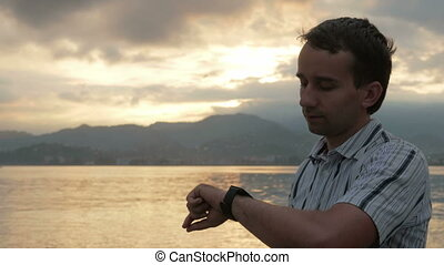 A man in a shirt checks messages on smart watch during the sunrise on the beach of the ocean and mountains. There is a dictation voice messages. Stunning colors of sky and rising sun