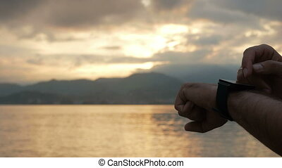 A man checks messages on smart watch during the sunrise on the beach of the ocean. Wonderful colors of the sky and the rising of the sun from behind the mountains. Close-up