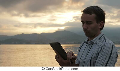 A man in a shirt checks messages on the tablet during the sunrise on the beach of the ocean.