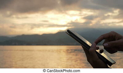 A man checks messages on the tablet during the sunrise on the beach of the ocean. Stunning colors of sky and rising sun. Close-up