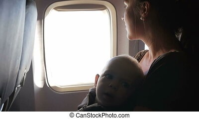 Baby sitting on mother's lap on an airplane during flight....