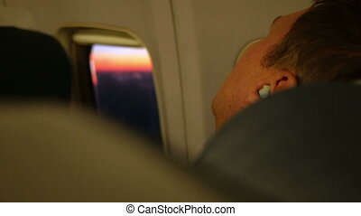 Young man resting on the plane during the flight. He sleeps in the headphones. The porthole beautiful sunrise.