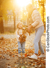 Mother and daughter throw up fallen leaves. Fun. - Family...