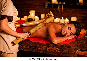 Young woman have bamboo sticks therapy massage.
