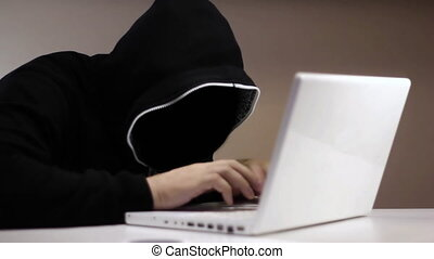 Anonymous hacker in black hood with a laptop white
