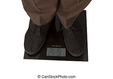 Man checking body weight on a weighing machine