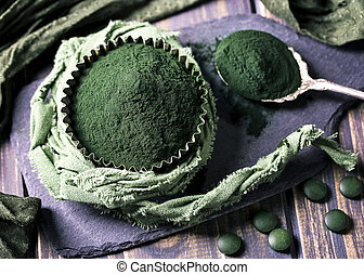Spirulina powder on a wooden background