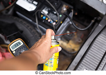 Mechanic holding aerosol cans spray oil for battery replacement