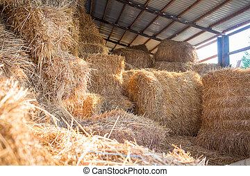 Hay stacks storage at farm haylof - Hay stacks and bales at...