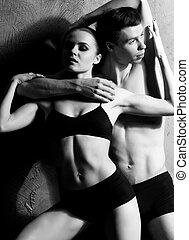 Couple of sporty ballet dancers performing in a studio -...