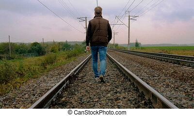 Man walking on the railroad - A man walks by rail to the...