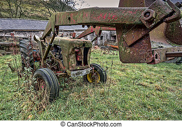 Derelict tractor - An old rusty derelict tractor parked in a...