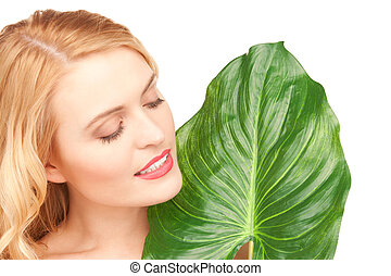 woman with green leaf over white