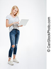 Full length portrait of a happy woman using laptop computer...