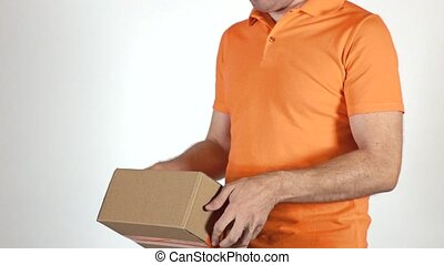 Courier in orange uniform tossing a small parcel. Light gray...