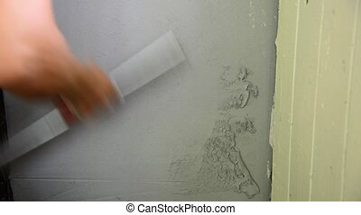 Workman plastering with a spatula wall