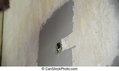 Plasterer plastering with a spatula wall near power socket -...